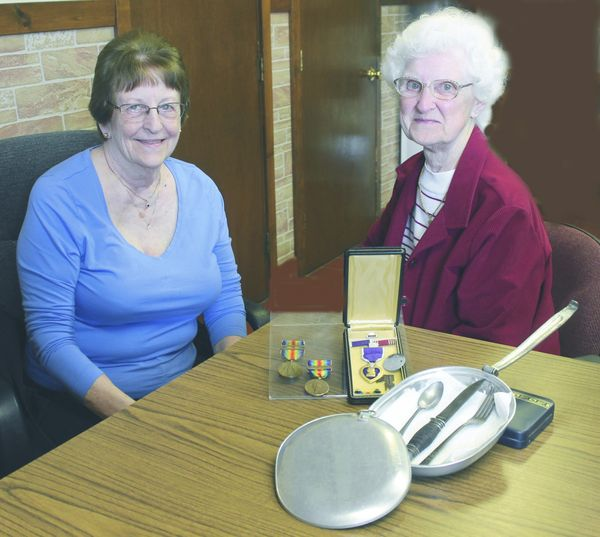 Displaying medals and a mess kit from their father's WWI service are Vera Gail Eppler (left) and Helen Meyer, daughters of Private Harold W. Lauchle, late of Huntersville.